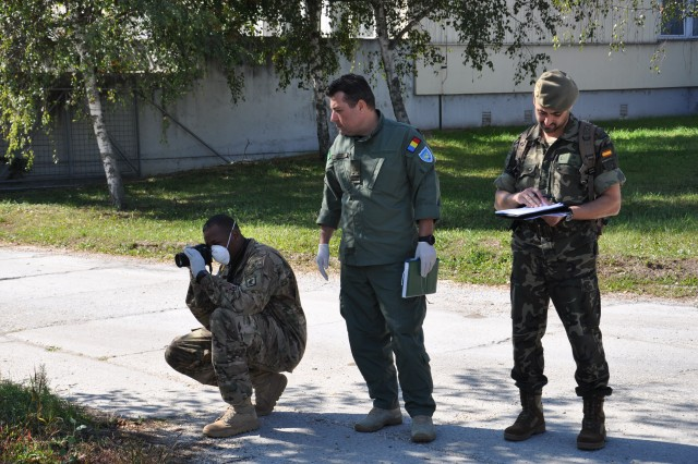 A U.S. Army paratrooper from the 173rd Airborne Brigade, along with NATO allies from Romanian and German forces, document a simulated IED site during a combined weapons intelligence course held at the NATO Counter-Improvised Explosive Device Center of Excellence in Szentendre, Hungary, Oct. 1, 2015.