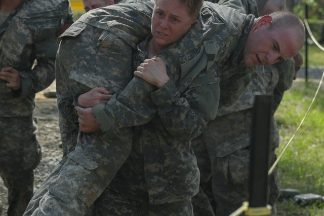 Maj. Lisa Jaster, an Army Reserve soldier, performs a fireman's carry on a simulated casualty during the Ranger Course on Ft. Benning, GA. The 37-year-old engineer and mother of two children, aged 7 and 3, is the first female Army Reserve officer to graduate the grueling combat leadership course, joining the ranks of fellow West Point graduates and Active Duty officers Capt. Kristen Griest, 26, and 1st Lt. Shaye Haver, 25.