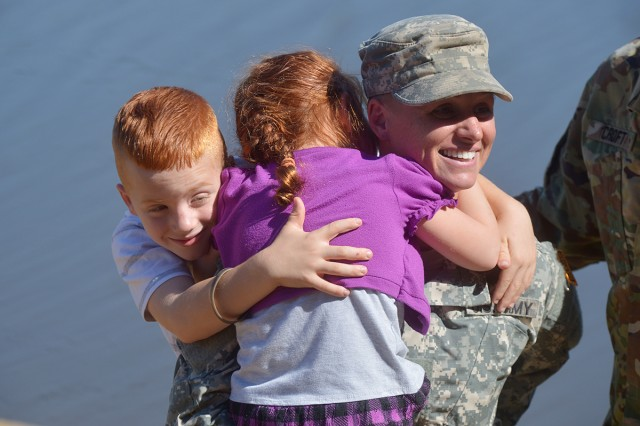 U.S. Army Maj. Lisa Jaster, a Reserve engineer officer in the Army Individual Mobilization Augmentee program, hugs her children after graduating from the Ranger course on Fort Benning, Ga., Oct. 16, 2015. Jaster is the third female, and the first female Reservist to win the prestigious recognition.