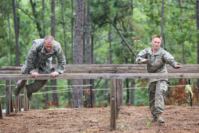 Maj. Lisa Jaster, right, tackles the hurdles at the Darby Queen obstacle course as part of training at the Ranger course on Fort Benning, Ga., June 28, 2015.