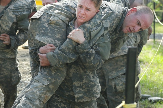 Maj. Lisa Jaster, an Individual Mobilization Augmentee officer, who serves with the U.S. Army Engineering and Support Center, carries a fellow Soldier during the Darby Queen obstacle course segment of the Ranger course on Fort Benning, Ga., April 26, 2015.