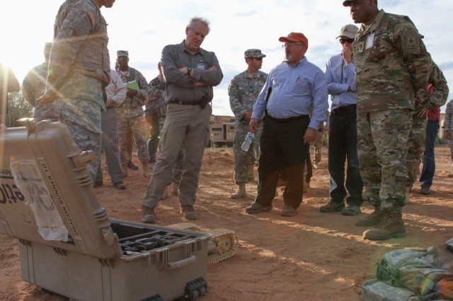 Out at the 4th Battalion, 17th Infantry Regiment, a Soldier briefs the (l to r) Under Secretary of Defense for Acquisition, Technology and Logistics, Hon. Frank Kendall, Program Executive Officer, Command, Control and Communications-Tactical, Gary Martin and Principal Military Deputy, Assistant Secretary of the Army, Acquisition, Logistics and Technology, Lt. Gen. Michael Williamson. The Soldier demonstrated various capabilities and explained the potential value added they may provide to the Warfighter during Network Integration Evaluation 16.1 at Fort Bliss, Texas.