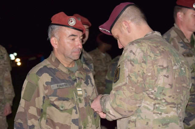 U.S. Army paratrooper Capt. Marc Levitt, assigned to the 173rd Airborne Brigade, pins the American Parachutist Badge on French Lt Col. Fabrice Chapuy, deputy commander of the French 11th Parachutist Brigade's 35th Parachutist Artillery Regiment, Oct. 16, 2015, as part of the wing exchange following the successful completion of a joint airborne operation on Juliet Drop Zone near Aviano, Italy. The 173rd Airborne Brigade, based in Vicenza, Italy, is the U.S. Army contingency response force in Europe and is capable of deploying ready forces to conduct the full range of military operations across the U.S. European, Africa and Central Commands' areas of operations within 18 hours. (U.S. Army photo by Sgt. Jason Hackworth)
