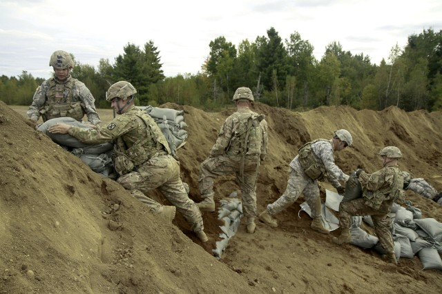 Soldiers assigned to B Company, 41st Engineer Battalion, 2nd Brigade Combat Team, move sand bags to fortify an individual fighting position during their platoon-level base defensive live-fire exercise Oct. 6 on Fort Drum's training area.