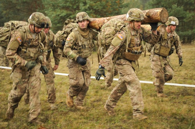 U.S. Soldiers with 1st Armored Brigade Combat Team, 3rd Infantry Division, carry logs at the maintenance site during the European Best Squad Competition held at the 7th Army Joint Multinational Training Command's Grafenwoehr Training Area, Germany, Oct. 20, 2015. The EBSC is an Army Europe competition challenging militaries from across Europe to compete and enhance teamwork with Allies and partner nations. The competition is multinational by design and involves units from 13 nations with 17 squads competing for the right to be Europe's Best Squad.
