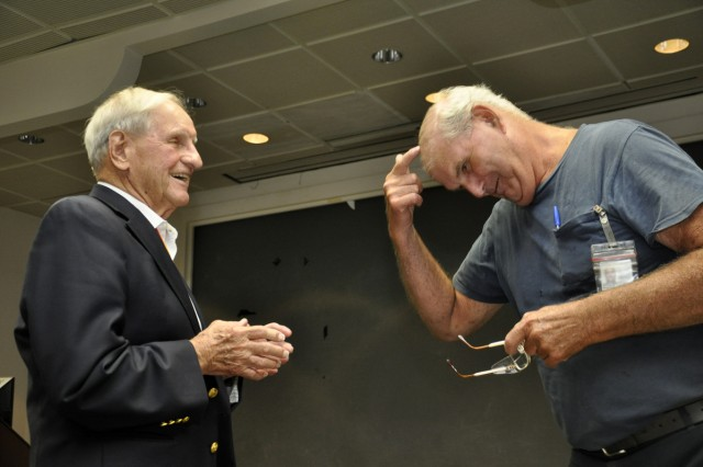 Master machinist Frank Taylor, right, shows Fred Clas one of the significant changes that has occurred, loss of hair, since they had last seen each other nearly 30 years ago.