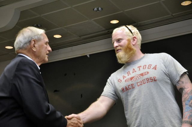 Fourth-year apprentice James Nowell thanking Fred Clas for his 40 years of service during Clas' visit to the arsenal in August 2015.