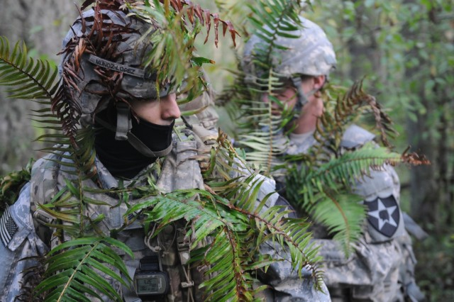 Spc. Spencer Secord, right, an intelligence analyst assigned to D Company, 14th Brigade Engineer Battalion, 2-2 ID (SBCT), helps camouflaged Sgt. Alfredo Munoz, a cryptologic linguist also assigned to D Company, during a cyber training exercise on Joint Base Lewis McChord, Wash., Oct. 20, 2015. The training integrates infantry ground units with cyber, signal and human intelligence collection capabilities, which gives units on the modern battlefield a broader capacity to search out and isolate their enemies in real time.