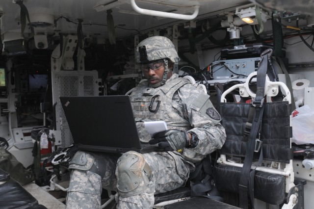 A cyber Soldier, assigned to the 780th Military Intelligence Brigade, prepares his equipment inside a Stryker vehicle during an integrated cyber exercise on Joint Base Lewis-McChord, Wash., Oct. 21, 2015.