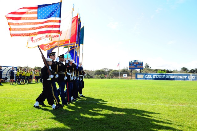 PRESIDIO OF MONTEREY, Calif. -- Defense Language Institute Foreign Language Center Joint Service Color Guard parade the colors across the pitch of the Otter Sports Complex, Cal State Monterey Bay, prior to the start of double header men's and women's collegiate soccer games during CSUMB's Military Appreciation Day, Oct. 18
