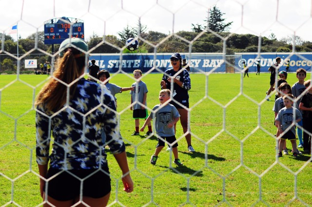 PRESIDIO OF MONTEREY, Calif. -- Otter Pups, a Cal State Monterey Bay sports fan club program from the Presidio of Monterey's Porter Youth Center, take shots on goal with members of CSUMB women's soccer team during half-time of the men's game during Military Appreciation Day.