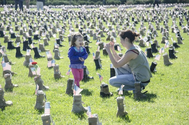 Stacy Babb takes a photo of her daughter Eva, 2, next to Sgt. John Daggett's boot on the 101st Airborne Division headquarters grounds. Babb said Daggett was her husband's best friend during their first deployment, so she let Eva pick a flower to put in the boot for him. Daggett is one of more than 7,000 service members represented in the Boots on the Ground memorial. This is the second year the display has been part of Military Survivor Appreciation Week at Fort Campbell, Oct. 15-18, 2015.