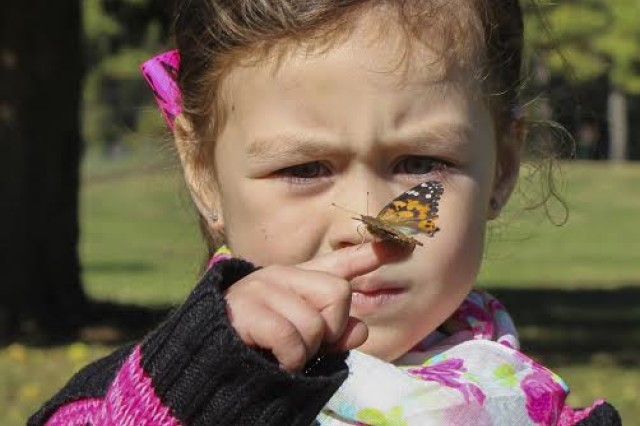 Yesenia Osoria, niece of the late Pfc. Marty Maiden, takes a close look at a butterfly during a butterfly release which was part of Fort Campbell's Military Survivor Appreciation Week, Oct. 15-18, 2015.