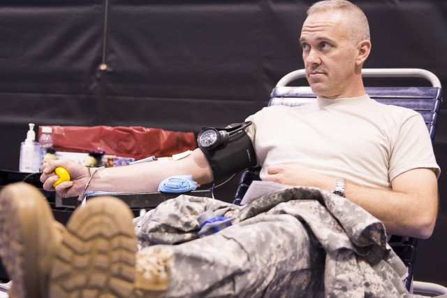 Army Lt. Col. Ryan Morgan, 3d U.S. Infantry Regiment (The Old Guard) deputy commanding officer, gives blood during the Army vs. Navy blood drive at the Fort Myer Fitness Center on the Fort Myer portion of Joint Base Myer-Henderson Hall Dec. 3, 2014. This year's blood drive, which is coordinated by the Armed Services Blood Program, will be held Nov. 10 at the Fort Myer Fitness Center.