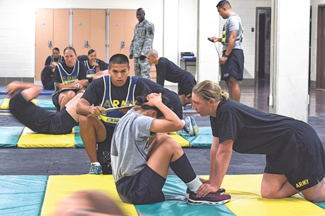 Staff Sgt. Ramon Juarez, Fitness Training Unit drill sergeant, monitors the sit-up portion of an Army Physical Fitness Test, to determine if the Soldier taking the test will train with the FTU or return to her unit.