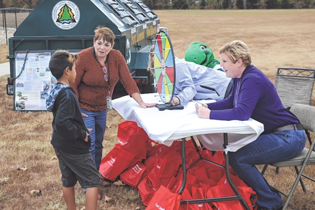 Judy Harmon, left, Tricia Littleton, center, and Heather Williams, right, all contractors with Colorado State University , Center for Environmental Management for Military Lands, ask 8-year-old Musashi Reyes questions about recycling.