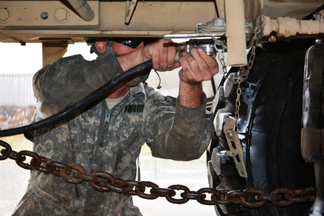 Spc. Adam Johnson, a wheeled vehicle mechanic assigned to Forward Support Company 62nd Engineer Battalion, connects the air hose from a tow vehicle to a simulated disabled vehicle during the Wheeled Vehicle Recovery Course at Regional Training Site Maintenance-Fort Hood, Texas, Oct. 22, 2015.