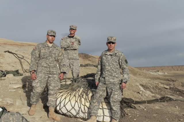 1st Battalion, 200th Infantrymen Staff Sgt. Jonathon Velarde, right, Sgt. Bryan Haworth and Spc. Alonzo Romero, left, pose for a photograph while they await the airlift of a 4,500-pound baby Pentaceratops skull encased in the plaster block between them.