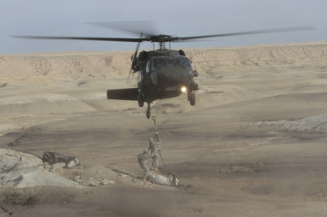 A Company C, 1st Battalion, 171st Aviation, UH-60 Blackhawk crew, consisting of pilots Maj. Daniel Purcell and Capt. Kevin Doo and crew chiefs Sgt. 1st Class Dennis Cahill and Sgt. Saul Monarez, airlift a unique slingload of a baby Pentaceratops dinosaur skull out of the Bisti/De-na-zin Wilderness Area, Oct. 29, 2015.
