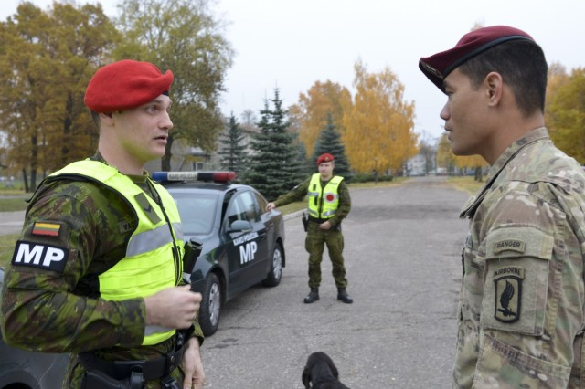 U.S. Army Capt. Helaman Fepuleai, commander, Company D, 1st Battalion, 503rd Infantry Regiment, 173rd Airborne Brigade, synchs the communication plan with a Lithuanian military policeman, in Marijampole, Lithuania, Oct. 25, 2015, prior to day two of ‪Operation Bayonet Thrust‬, a multinational convoy bringing the Americans home to Italy after five month training in Lithuania as part of Operation Atlantic Resolve. (U.S. Army photo by Sgt. A.M. LaVey/173rd ABN PAO)