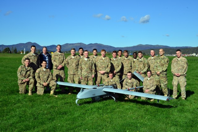 U.S. paratroopers, assigned to 54th Brigade Engineer Battalion, 173rd Airborne Brigade, pose for a group photo behind them RQ7B Shadow Technical unmanned aircraft system during Exercise Rock Proof V at Aeroclub Postonja in Slovenia, Oct. 20, 2015.