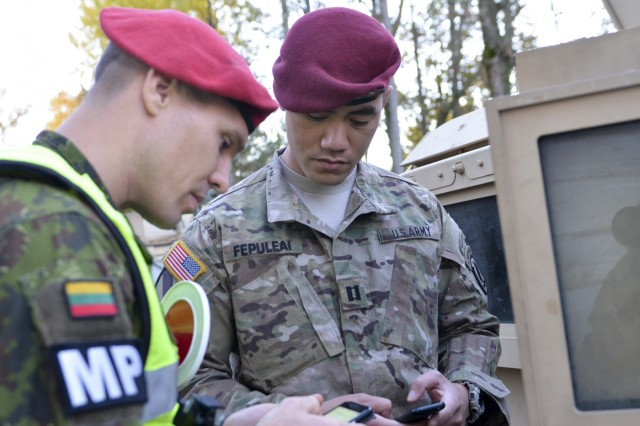 U.S. Army Capt. Helaman Fepuleai, commander, Company D, 1st Battalion, 503rd Infantry Regiment, 173rd Airborne Brigade synchs communication with a Lithuanian army Sgt. Albnas Kondrotas, a military policeman, in Panevezys, Lithuanian, Oct. 24, 2015, prior to day one of Operation Bayonet Thrust, a multinational convoy bringing the Americans home to Italy after five month training in Lithuania as part of Operation Atlantic Resolve.