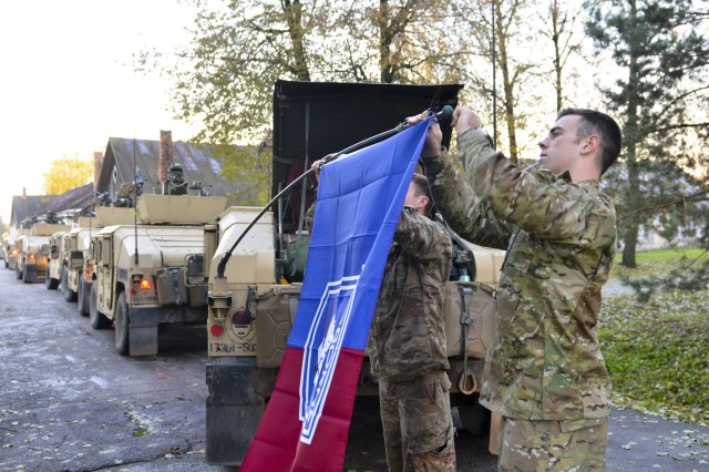 U.S. Army paratroopers from Company D, 1st Battalion, 503rd Infantry Regiment, 173rd Airborne Brigade, tie a brigade flag on their vehicle on day one of Operation Bayonet Thrust, Panevezys, Lithuania, Oct. 24, 2015. Bayonet Thrust is name of the multinational convoy bringing the 173rd home from a rotation in the Baltics in support of Operation Atlantic Resolve. (U.S. Army photo by Sgt. A.M. LaVey/173 ABN PAO)