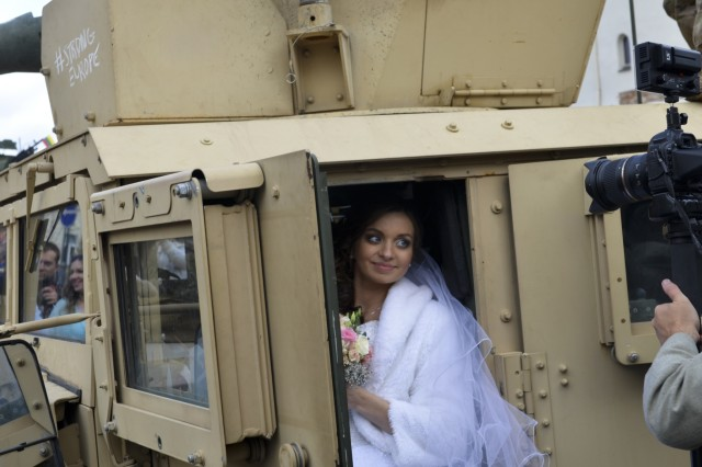 A newly-wed bridge poses in a 173rd Airborne Brigade humvee, during a community event on day one of Operation Bayonet Thrust, Vilnius, Lithuania, Oct. 24, 2015. Bayonet Thrust is name of the multinational convoy bringing the 173rd home from a rotation in the Baltics in support of Operation Atlantic Resolve. (U.S. Army photo by Sgt. A.M. LaVey/173 ABN PAO)