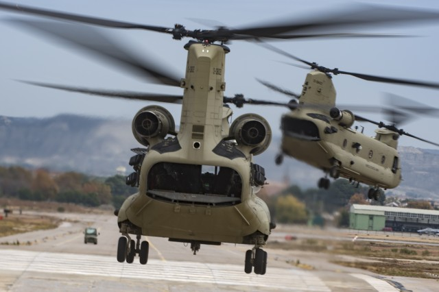 Two CH-47F Chinook helicopters, from Hotel Company, 1st Battalion, 214th Aviation Regiment, 12th Combat Aviation Brigade, take off en route to retrieve air assault troops in preparation for an air assault mission as part of NATO Exercise Trident Juncture 2015 in Zaragoza, Spain, Nov. 3, 2015. (U.S. Army photo by Sgt. Thomas Mort)