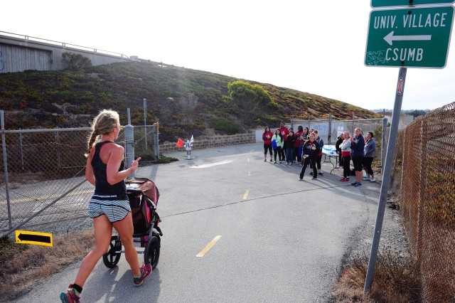 PRESIDIO OF MONTEREY, Calif. -- A runner with a stroller passes by volunteers on the 10K course during the Honor Our Fallen 5K & 10K Run/Walk event held at Fort Ord Dunes State Park, Oct. 24.