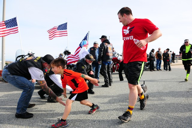 PRESIDIO OF MONTEREY, Calif. -- A young participant in the third annual Honor Our Fallen Run/Walk event Oct. 24 reaches out his hand to members of the American Legion Riders Chapter 31 who greeted and cheered runners approaching the finish line.