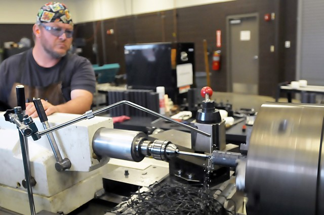 This contracted employee uses a lathe to drill out an item that will eventually be used for a grenade launcher weapons rack at Fort Benning, Georgia. Creating solutions for Soldiers is one of the many missions of the Logistic Readiness Centers. (Photo by Jon Michael Connor, ASC Public Affairs)