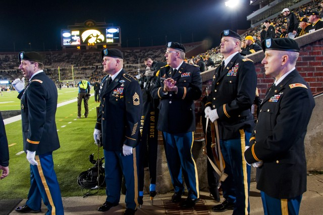 Lt. Col. Brad Cook (right), inspector general, U.S. Army Sustainment Command, waits to post the colors with his fellow University of Iowa alumni at the start of the Hawkeyes' annual football game against the Minnesota Golden Gophers at Kinnick Stadium, Iowa City, Iowa, Nov. 14. (Photo by Kevin Fleming, ASC Public Affairs)