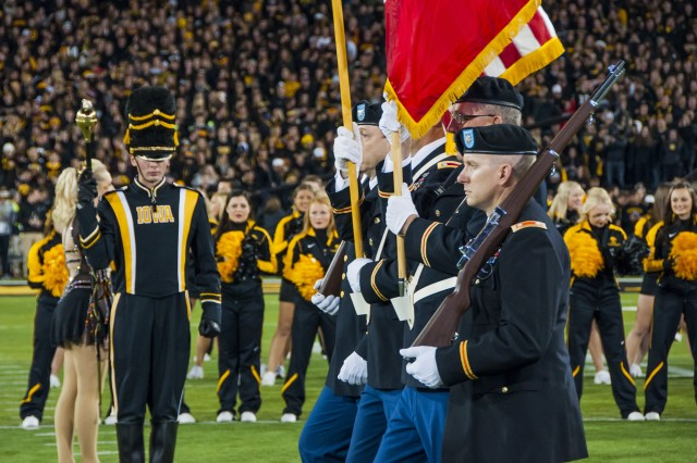 Lt. Col. Brad Cook (right), inspector general, U.S. Army Sustainment Command, posts the colors with his fellow University of Iowa alumni at the start of the Hawkeyes' annual football game against the Minnesota Golden Gophers at Kinnick Stadium, Iowa City, Iowa, Nov. 14. (Photo by Kevin Fleming, ASC Public Affairs)