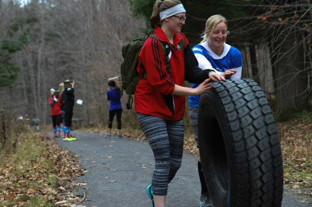 "Spouses of Soldiers assigned to 2nd Brigade Combat Team ""Commandos,"" move a tire around the 2-mile trail during the Commandos Veteran Day challenge Nov.11, on Fort Drum."