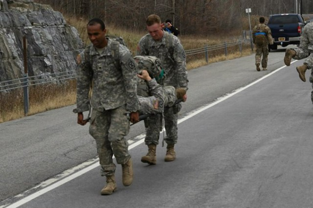 "Soldiers assigned to 2nd Brigade Combat Team ""Commandos,"" us a litter and fireman carry to move team members acting as simulated casualties up a steep hill to a causality collection point during the Commando Veterans Day challenge Nov. 11, on Fort Drum."