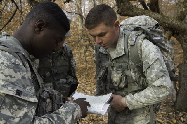 Spc. Kevin O'Brien (right), health care specialist, C Company, 210th Brigade Support Battalion, 2nd Brigade Combat Team, reads a military map Nov. 5, during their Rough Terrain Evacuation Course held at Camp Ethan Allen Training Site, Jericho, Vermont. O'Brien, who acted as the team's squad leader, was responsible for leading his team through three miles of mountainous Vermont wilderness to the medical extraction point.