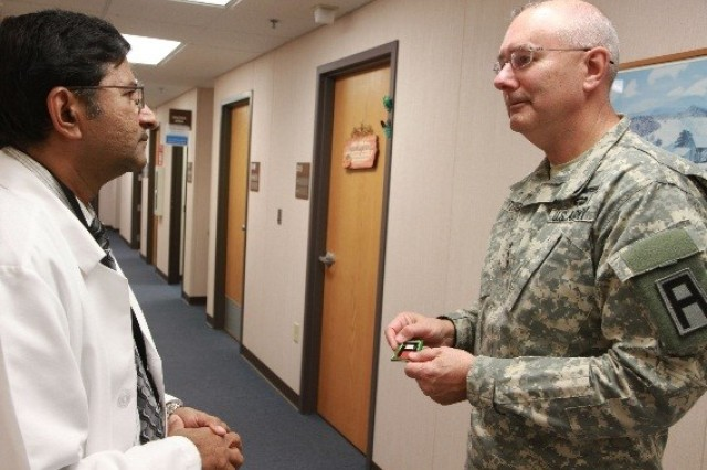 Lt. Gen. Michael Tucker, First Army commanding general, presents a First Army challenge coin to Dr. Ananda Reddy, lead physician of the Quad Cities Veterans Affairs Community Based Outpatient Clinic in Bettendorf, Iowa, Nov. 9. During Tucker's visit to the annex outpatient clinic of the Iowa City VA Health Care System, he spoke with registered nurses, doctors and medical technicians and learned what the clinic does for veterans.