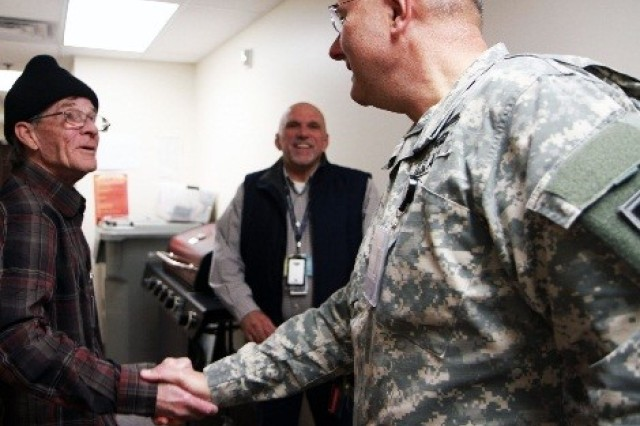 """Lt. Gen. Michael Tucker, First Army commanding general, shakes hand with Navy veteran Daniel Drehoble during a visit to the Veterans Affairs Homeless Outreach Center in Rock Island, Illinois, Nov. 10. Drehoble, who takes four buses each day to volunteer at the outreach center, said, """"It gives me pleasure to help other veterans out by organizing the (clothing) closet so they can find the items they need."""""""