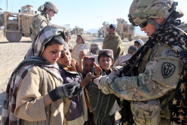 A Soldier with the 504th Military Intelligence Brigade interacts with Afghan children during an overseas deployment recently. The brigade has deployed to Iraq, Afghanistan and Kosovo, and also played a role in World War II, providing intelligence collection and analysis to battlefield and theater commanders.