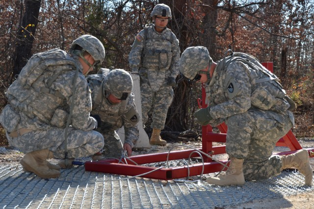 Soldiers, from the 509th Clearance Company, 5th Engineer Battalion, assemble a field expedient, non-lethal vehicle arresting barrier to field test its ease of use and effectiveness, Nov. 10, 2015.