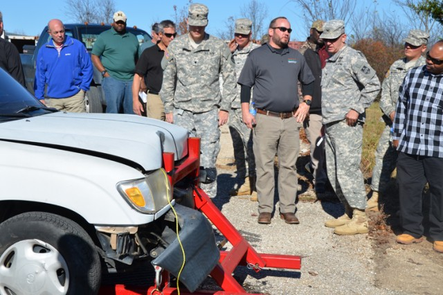 Engineers and spectators inspect the damage to a remote-test vehicle following a demonstration of the field-expedient, non-lethal vehicle arresting barrier.