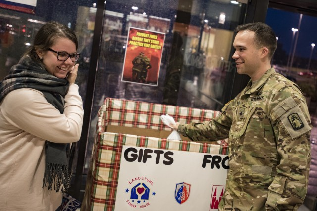 A 12th CAB Soldier and his wife shown donating a bag of household items just outside of the Ansbach Commissary. Over 50 Soldiers and Family members from 12th Combat Aviation Brigade came together to collect gifts for the Diakonie Neuendettelsau Orphanage and food items for the Landstuhl Fisher House, November 20-22, 2015, at the Ansbach AAFES Post Exchange and Commissary.