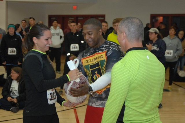 Gabriella Bermudez receives a turkey from Command Sgt. Maj. Tyson Goolsby, U.S. Army Garrison Fort Leonard Wood command sergeant major, and Col. Andy Herbst, U.S. Army Garrison Fort Leonard Wood commander, during the awards ceremony following Saturday's Turkey Trot 5k/10k run. Bermudez was the overall female winner of the 5k, finishing in 22:07.