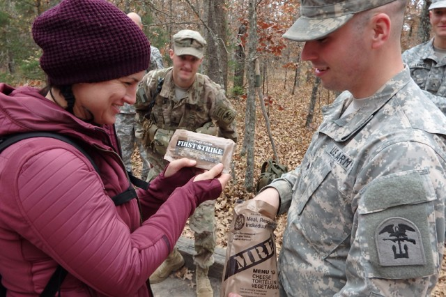 Gina Carano inspects a cheese tortellini MRE presented by Spc. Kevin McGowan, 169th Engineer Battalion.