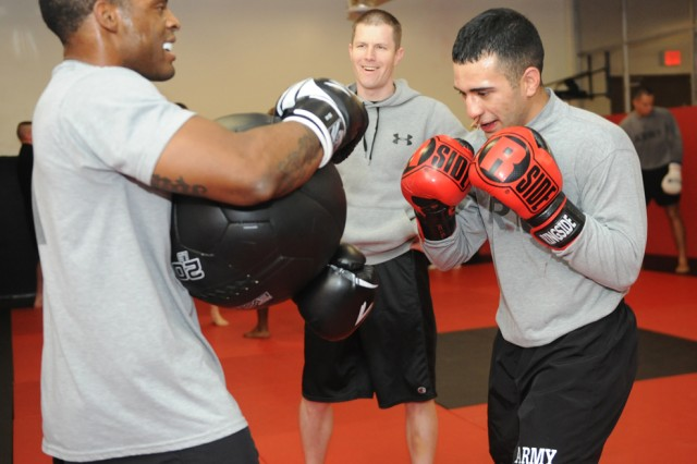 Staff Sgt. Harold Parham, left, 92nd Military Battalion, holds a medicine ball for Spc. Hector Leon, 92nd MP Bn., as coach Capt. Geoffrey Uhal watches the fighter's boxing form and footwork.