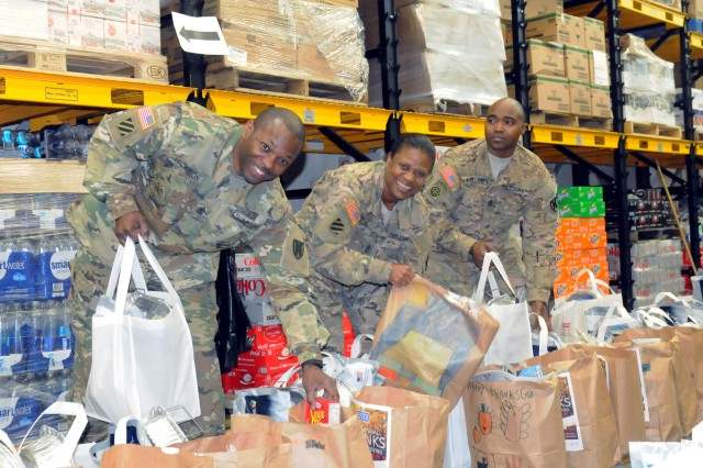 Sgt. Maj. Robert Hickson (left) of the 21st Theater Sustainment Command's 1st Human Resources Sustainment Center, Sgt. Maj. Crecencia Jeter, also with the 1st Human Resources Sustainment Center, and Sgt. Maj. Sean Miller, the Theater Sustainment Command operations sergeant major, prepare groceries for junior enlisted during a Thanksgiving care package distribution conducted, Nov. 21, 2015, in Kaiserslautern, Germany.