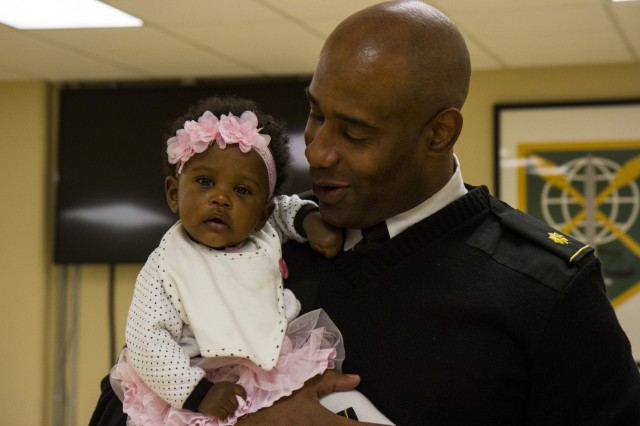 Maj. Micah Ramseur, a logistics officer with the 200th Military Police Command, shares a moment with his 7-month-old daughter, Michyla, during his promotion ceremony Nov. 24, at a U.S. Army Reserve center at Fort Meade, Md. Of Baltimore, Ramseur stressed the importance of family and the roles they play in a Soldier's career during his promotion speech. (U.S. Army photo by Sgt. Marc Loi)