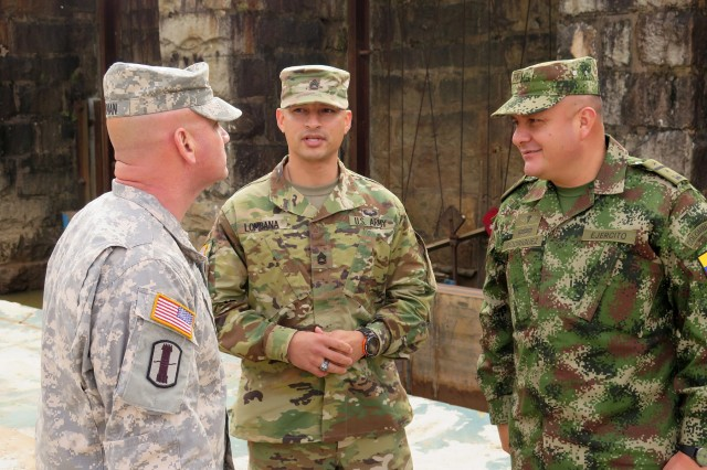 U.S. Army Lt. Col. Christopher Hyman, left, executive officer with the South Carolina Army National Guard's 59th Troop Command, answers questions from Colombian army Lt. Col. Hernando Rodriguez through Army National Guard Sgt. 1st Class Alexander Lombana at the Columbia Canal in South Carolina, Nov. 17, 2015.