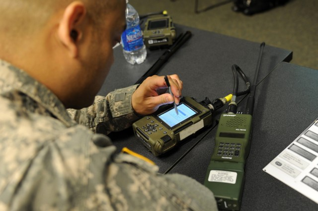 A Soldier programs a simple key loader, which allows radios to communicate securely between vehicles.